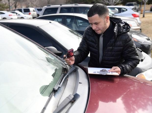 Insurance adjuster Juan Vazquez takes pictures ...
