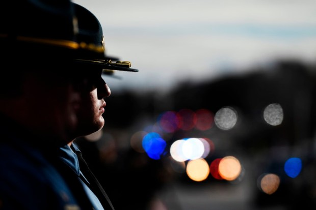 Law enforcement officers watch the funeral procession for Douglas County sheriff's Deputy Zackari Parrish on Jan. 5. Parrish was shot and killed while attempting to place Matthew Riehl under a mental health hold on Dec. 31 at Riehl's apartment in Highlands Ranch.