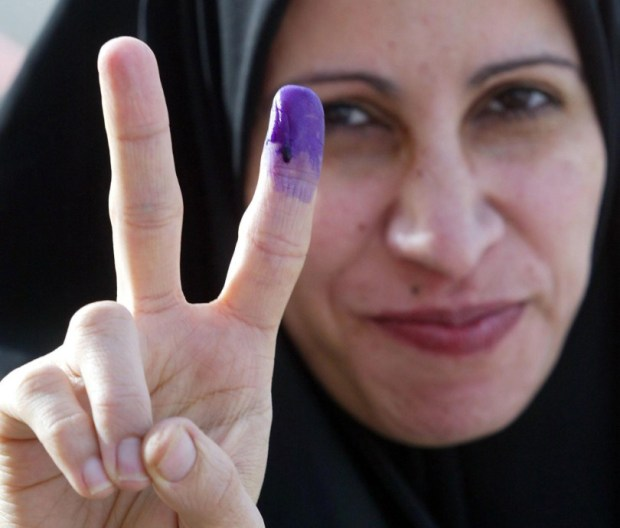 An Iraqi woman holds up her hand and shows a purple finger, indicating she has just voted, on Jan. 30, 2005.