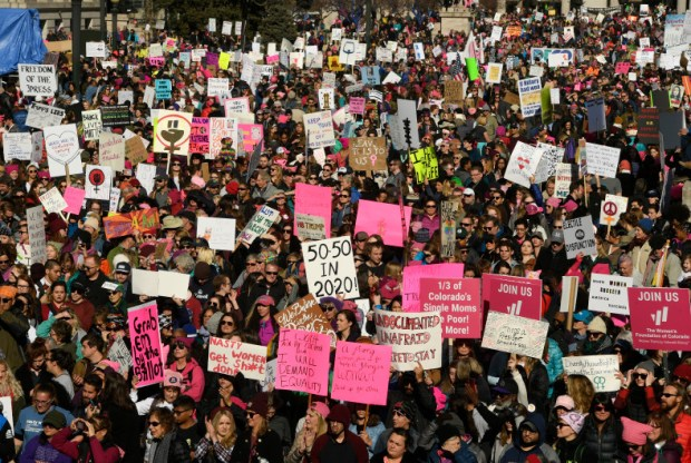 Thousands of people hold up signs in Denver's Civic Center last Saturday after taking part in the Denver Women's March.
