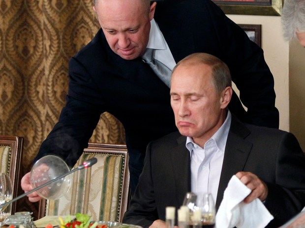 Yevgeny Prigozhin, a wealthy Russian businessman and restaurateur, serves food to Vladimir Putin at Prigozhin's restaurant outside Moscow on Nov. 11, 2011. Progozhin, along with 12 other Russians and three Russian organizations, has been charged by the U.S. government as part of a vast and wide-ranging effort to sway political opinion during the 2016 election.