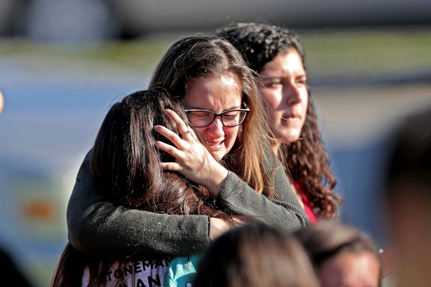 Students embrace after Wednesday's mass shooting at Marjory Stoneman Douglas High School in Parkland, Fla.