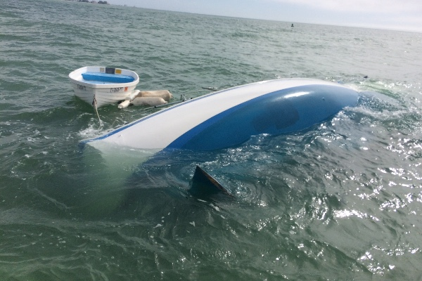A portion of Nikki Walsh and Tanner Broadwell's sailboat, the Lagniappe, is visible above the water in a channel just off Madeira Beach, Fla. The boat struck a submerged object and sank on Feb. 7, 2018.