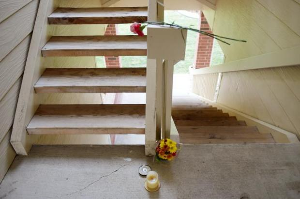 Flowers and candles lay in a second-floor stairwell in Building H at The Shores at McIntosh Lake two mornings after the stabbing death there of 20-year-old Makayla Grote.