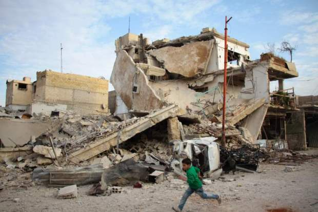 A Syrian boy runs past a destroyed building during airstrikes by regime forces in the rebel-held town of Douma, on the outskirts of the capital Damascus, last month.
