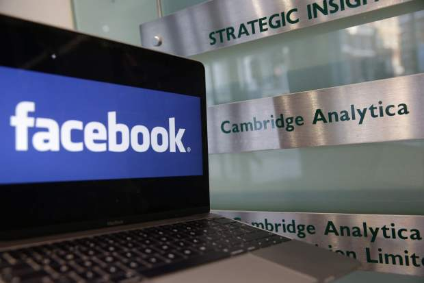 A laptop showing the Facebook logo is pictured at the offices of Cambridge Analytica in London on Wednesday.