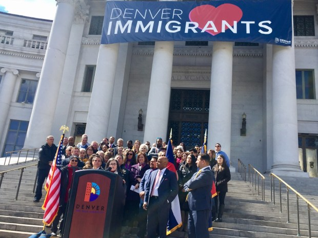 City Attorney Kristin Bronson discusses how the new Denver Immigrant Legal Services Fund will work during a news conference launching the long-discussed initiative on March 19, 2018, on the steps of the City and County Building. Mayor Michael Hancock and City Councilman Paul López are at right in the front.