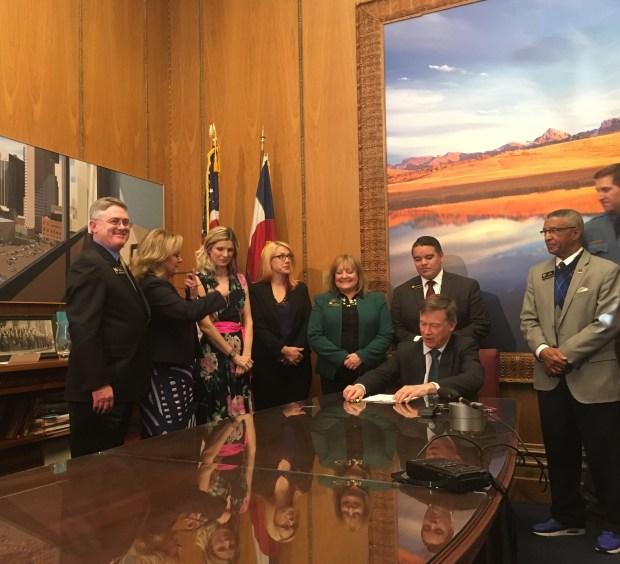 Colorado Gov. John Hickenlooper signs Senate Bill 148 into law.