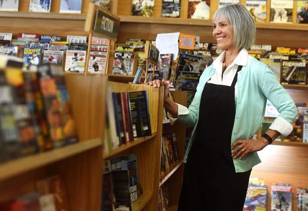 Store manager Kimberly Bode smiles as she stands among books at Woody's Newsstand, 942 9th Ave. in Greeley. After 81 years Woody's will be closing.