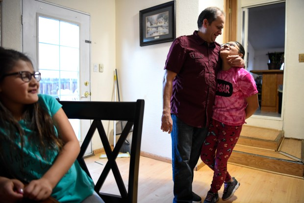 "AURORA, CO - FEBRUARY 12: Rudi Lopez-Cordova hugs his daughter, Allison, as his other his daughter, Jazlyn, sits nearby at their home on Monday, March 12, 2018. Cordova has Temporary Protected Status, but that will expire in September 2019, leaving him and others in Limbo as they will no longer be able to reside or work in the United States. Cordova was born in El Salvador and came to the United States in 1999 to pursue more opportunities for work. He currently works at PF Chang's and Whole Foods and owns a home in Aurora. He said that a relative living in El Salvador works in a factory making shirts for just $8 a day. Of his two youngest children, who were born in the United States and are citizens, he says, ""This is their world. This is the only world they know."" (Photo by AAron Ontiveroz/The Denver Post)"