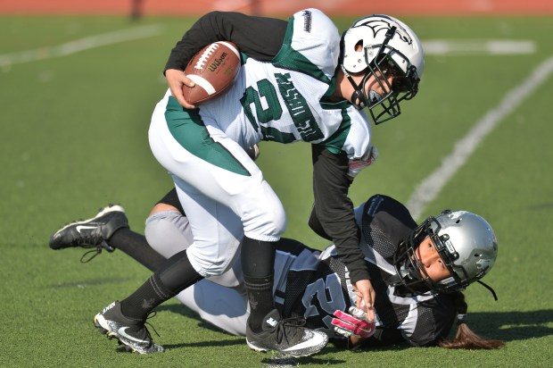 Leilani Caamal of Montbello Futures, bottom, tackles Brad Edmands of George Washington Futures during 1st quarter of the game at All City Stadium in Denver on Saturday, April 7, 2018.