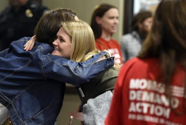 Moms Demand Action members Sarah, center, hugs Melissa, who both didn't give their last names, after the Boulder City Council unanimously passed the ban on assault weapons on Tuesday in Boulder.