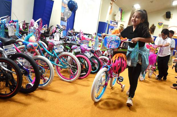 Crystal Valdez, 8, wheels her bike out of the gym during a special assembly for students with good attendance on Wednesday at Madison Elementary School, 500 24th Ave. in Greeley. The bikes were donated to the school by the Roche family.