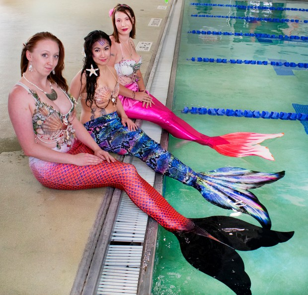 In this  May 1, 2018 photo, Members of a pod of real-life mermaids based in Pueblo, perch on the edge of the Colorado State University-Pueblo pool before a practice session in Pueblo, Colo. Pictured from left: Pixie Wright, Jaclyn Gutierrez and Camber Mauth.