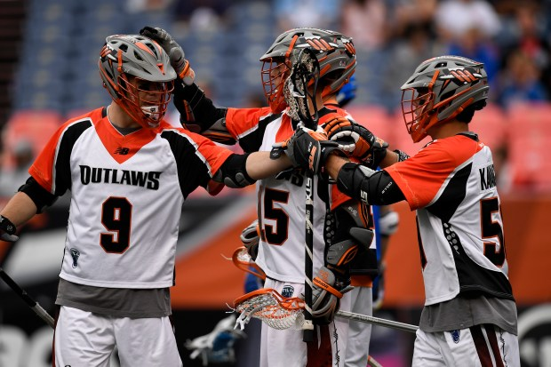 Denver Outlaws players celebrate a third quarter goal by midfielder Jeremy Sieverts, during their home opener against the Charlotte Hounds at Mile High Stadium on May 7, 2017 in Denver, Colorado.