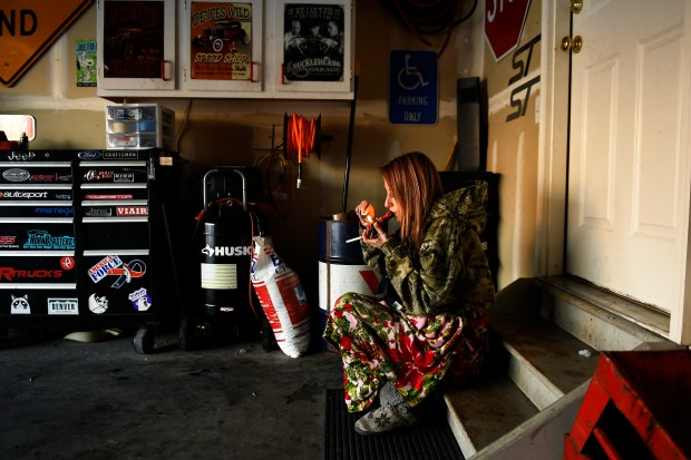 Sarah Janeczko, 21, smokes a bowl in the garage of her new home January 23, 2018 in Aurora, Colorado. Her boyfriend Anthony and other previous roommates, moved in together and they feel they have found a home for themselves and their dogs.