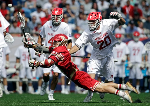 Denver's Austin French shoots as Maryland's Dylan Gaines (41) and Matthew McIiroy (20) defend during the first half of an NCAA college Division 1 lacrosse semifinal, Saturday, May 27, 2017, in Foxborough, Mass.