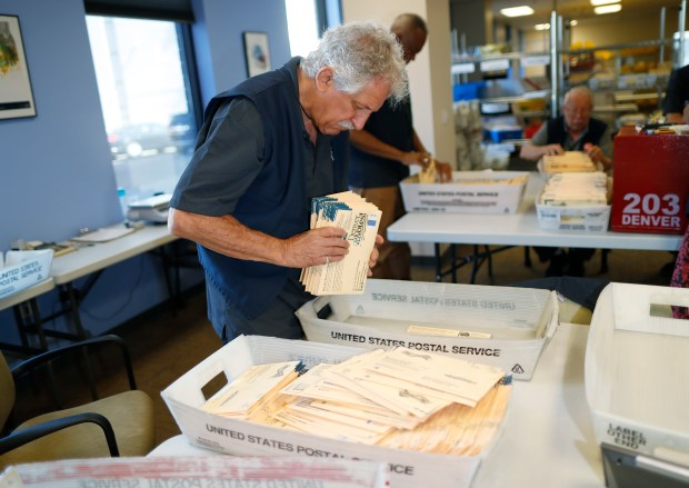 Election judge Michael Plous works as judges organize primary election ballots for counting as they arrive at the Denver Elections Division headquarters early Tuesday, June 26, 2018, in Denver. (AP Photo/David Zalubowski)