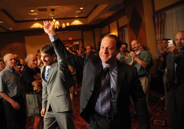 Jared Polis walks in hand-in-hand with his partner Marlon Reis as he celebrates with supporter during the primary election party at Renaissance Hotel in Broomfield.