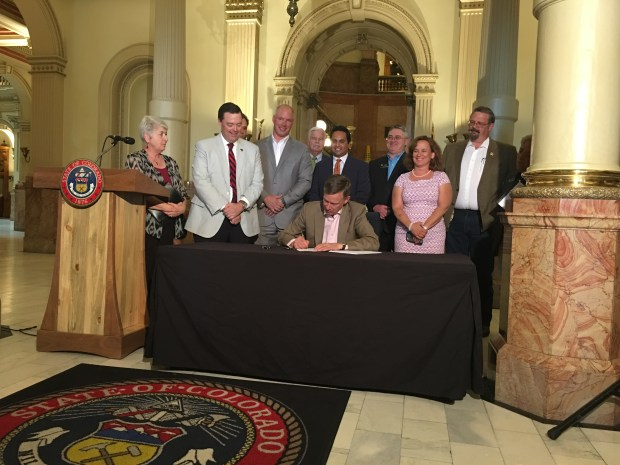 Gov. John Hickenlooper, sitting, is surrounded by state lawmakers as he signs Senate Bill 200 on Monday, June 4, 2018.