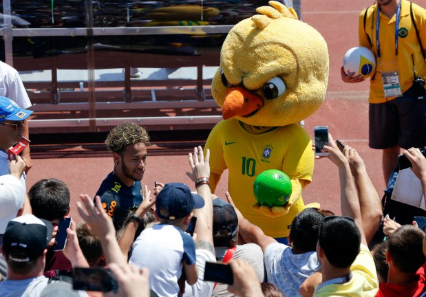 In this Tuesday, June 12, 2018 file photo Brazil's mascot holds a soccer ball as fans cheer Brazil's Neymar as he leaves a training session in Sochi, Russia.