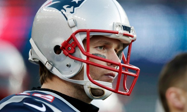 In this Jan. 21, 2018, file photo, New England Patriots quarterback Tom Brady watches from sideline during the first half of the AFC championship NFL football game against the Jacksonville Jaguars in Foxborough, Mass.