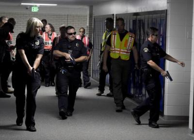 Broomfield police officers, Meredith Durham, left, Josh Vaughn, and Chrissy McCain, look for the shooter during an active-shooter drill. The Broomfield Police Department and Boulder Valley School District held the joint training session at Broomfield High School.