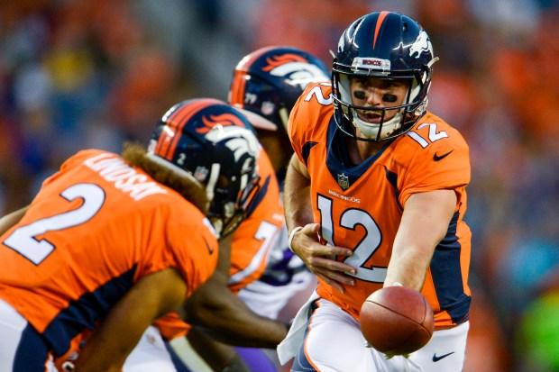 quarterback Paxton Lynch #12 hands the ...