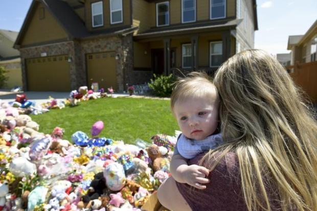 Thornton resident Rebecca Miller and her 5-month-old son,Grant, visit the memorial in front of the Watts home on Wednesday. A host of media and well-wishers have descended on the Wyndham Hill neighborhood in Frederick in the wake of the murders of Shanann Watts and her daughters, Bella and Celeste.