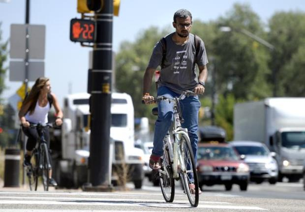 University of Colorado doctoral program student Abhijit Suresh rides his bicycle across 28th Street Wednesday while heading eastbound on Arapahoe Avenue in Boulder. City Council advanced plans to revamp Arapahoe to better suit bus, bike and pedestrian travel during a Wednesday meeting.