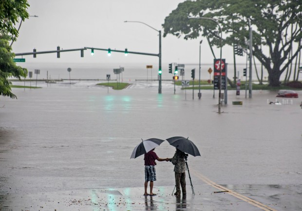 People stand near flood waters from ...