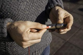 A man charging an electronic cigarette in the park