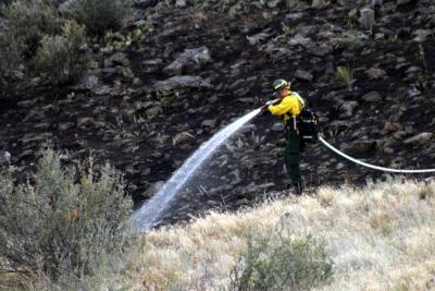 A firefighter sprays water on the perimeter of a small wildfire that was caused by lightning Friday afternoon near Carter Lake.