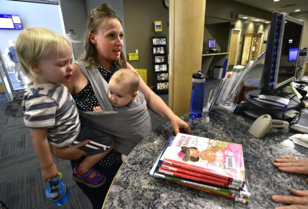 Kabrina Budwell checks out books with her son Ahldenn, 2, and daughter Alianah, 5 months, at the Mamie Doud Eisenhower Library in Broomfield Sept. 13.