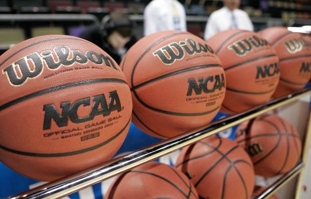 Basketballs sit in a rack ...