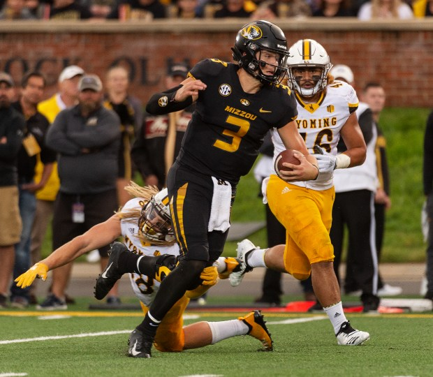 Missouri quarterback Drew Lock, center, scrambles ...