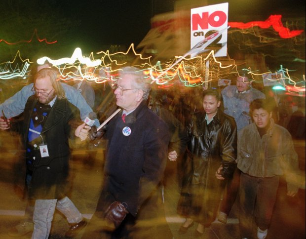 Colorado Gov. Roy Romer, front, carries a placard as he walks with protesters from a downtown Denver hotel to the west steps of the State Capitol to take part in a protest against the passage of the anti-gay legislation called Amendment 2 in this Nov. 4, 1992 photo.