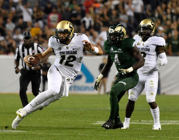 Colorado Buffaloes quarterback Steven Montez (12) side-steps in front of Colorado State Rams cornerback Rashad Ajayi (4) on his way to the end zone for a touchdown in the first quarter during the Rocky Mountain Showdown at Broncos Stadium at Mile High Aug. 31, 2018.