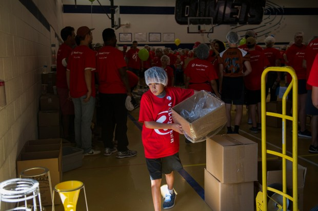 Collin Castanon, 9, carries a box, ...