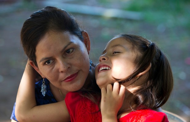Araceli Ramos holds her 5-year-old daughter, ...