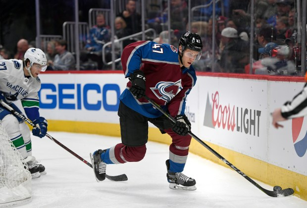 Colorado Avalanche center Dominic Toninato (47) drives the puck behind Vancouver Canucks goal and defenseman Ben Hutton (27), left, during the first period of the Avalanche game at Pepsi Center on Feb. 26, 2018 in Denver.
