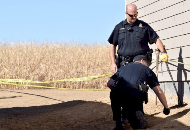 Greeley police officers use a metal detector to search the exterior of a west Greeley home for a bullet that wounded a man during an early Monday morning shooting.