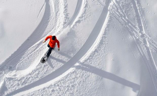 A snowboarder cuts a fresh line ...