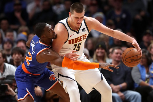 Nikola Jokic (15) of the Denver Nuggets is guarded by Noah Vonleh (32) of the New York Knicks at the Pepsi Center on Jan. 1, 2019 in Denver.