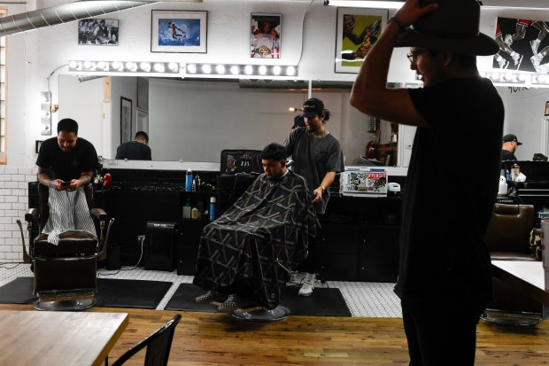 "Barber Josue ""Sway"" Navarro (center) works ..."