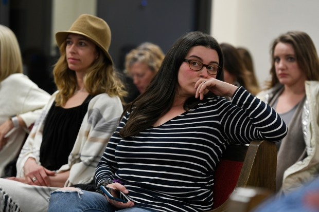 Megan Lombardo, right with stripes, listens ...