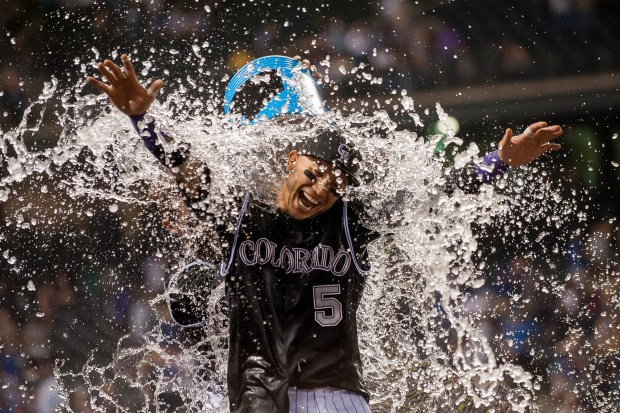 Carlos Gonzalez of the Colorado Rockies is drenched by a teammate after hitting a walk-off 2-run home run to put the Rockies ahead of the Dodgers 8-6 at Coors Field on Sept. 26, 2015 in Denver.