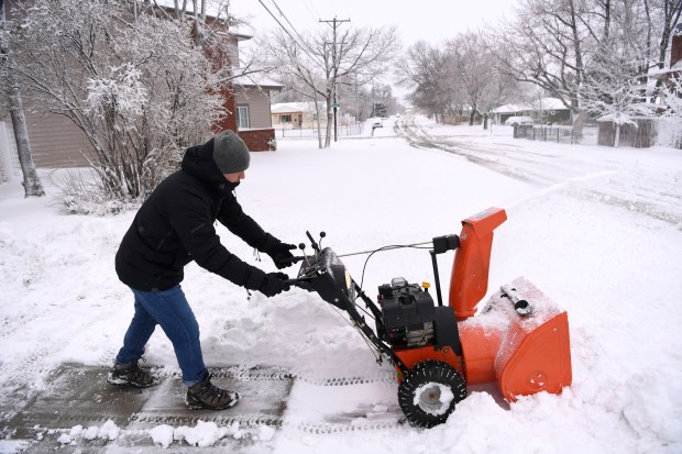 Michael McMahon uses a snow thrower ...
