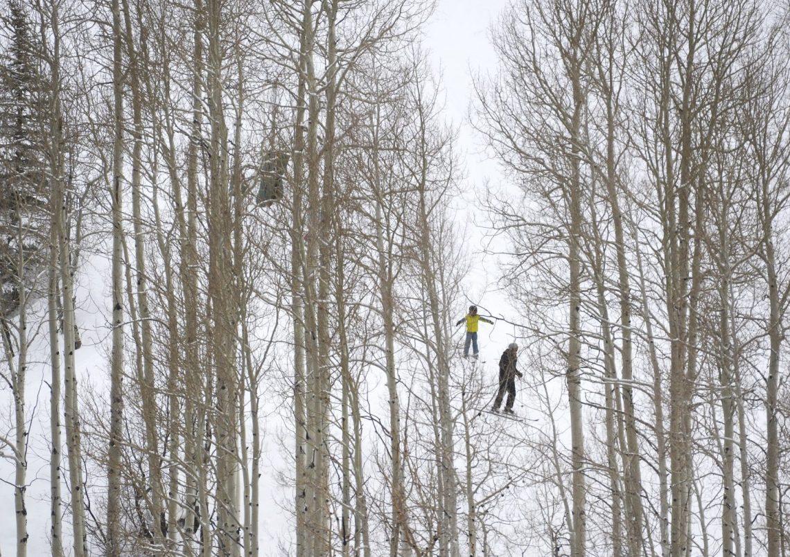 Skiers head down a run along ...