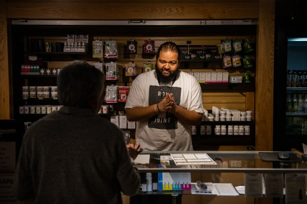 Budtender Isaiah Riley assists a customer ...
